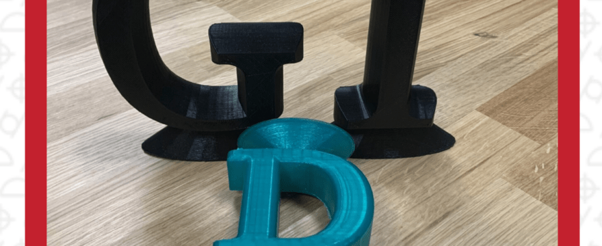 3D Printed capital letters black G, black T, blue D laying down on table top