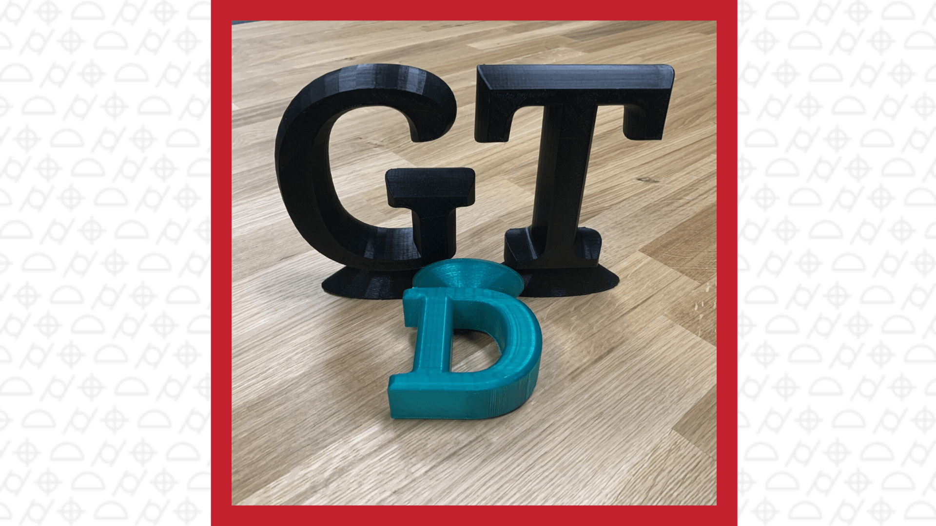 3D printed capital letters black G, black T, smaller blue D laying down on the table