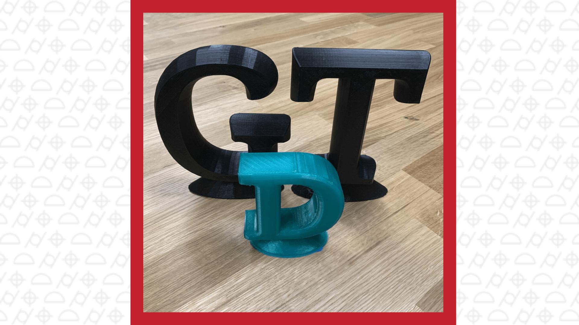 3D printed capital letters black G, black T, smaller sized blue D
