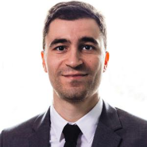 Sylvere Krima in gray suit, white shirt, dark tie