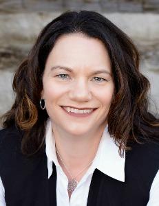 Jennifer Herron CEO wearing navy blue jacket, light blue shirt, with long dark hair